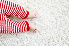 Close-up of baby body and legs in red Santa Clause trousers on Christmas. Close-up of baby body and legs in red Santa Clause trousers. New born child, little Stock Images