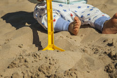Close up baby boy playing with sand toys at the beach. Stock Photos