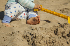 Close up baby boy playing with sand toys at the beach. Stock Photo