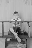 Close-up, baby boy sitting on a big plane, black and white Royalty Free Stock Photo