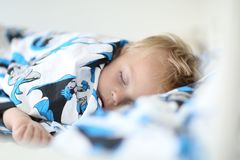 The boy boy is sleeping on a cute bedding royalty free stock image