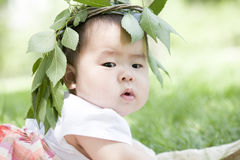 Close-up of a baby. A Chinese baby is on grass with a branch hat on head Royalty Free Stock Photography