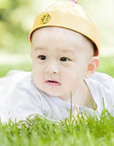 Close-up of a baby. A Chinese baby on grass with a cap on head Stock Images