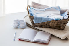 Close up of baby clothes for newborn and notebook Royalty Free Stock Photography