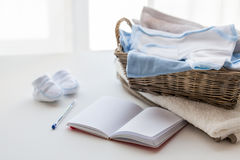 Close up of baby clothes for newborn and notebook Royalty Free Stock Image