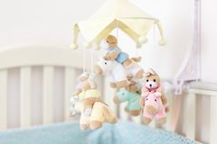 Close-up baby crib with musical animal mobile at nursery room. Hanged developing toy with plush fluffy animals. Happy parenting an. D childhood, expectation Stock Photos