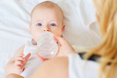 Close-up of baby eating food, water bottle. Mum feeds the child. Stock Photo