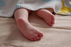 Close up of baby feet peeking out of blanket. The child is sleeping royalty free stock photography