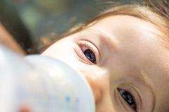 Close up of baby girl drinking milk from baby bottle. stock photography