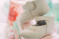 Close up of baby girl elegant white shoes with warm modern colors and style during babyshower. Toys and gifts for newborn baby royalty free stock image