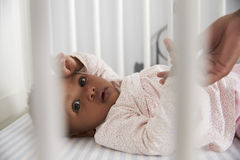 Close Up Of Baby Girl Lying In Nursery Cot Royalty Free Stock Image