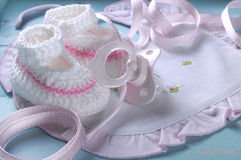 Close up of baby girl nursery booties, dummy and bib - close up Royalty Free Stock Image