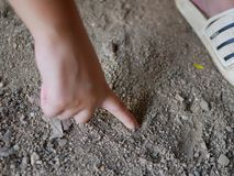 Baby hand drawing on a sandy ground. Close up of baby hand drawing on a sandy ground royalty free stock images