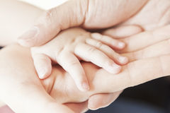 Close-up of baby hand into parents hand Stock Photo