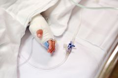 Close up baby hand on patient`s bed in hospital with saline intravenous. Baby admitted at hospital. Kid patients have IV tube.  royalty free stock images