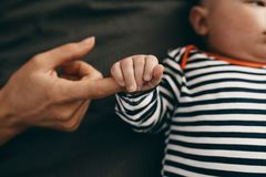 Close up of a baby holding the hand of his mother stock image