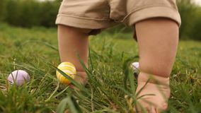 Close-up of baby legs. A child is looking for Easter eggs in the grass. Happy easter family stock footage