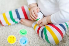 Close-up of baby playing playing with educational colorful shape sorter toy. Close-up of baby playing with educational toys at home or nursery. Happy healthy Royalty Free Stock Photography