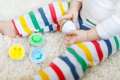 Close-up of baby playing playing with educational colorful shape sorter toy. Close-up of baby playing with educational toys at home or nursery. Happy healthy stock images