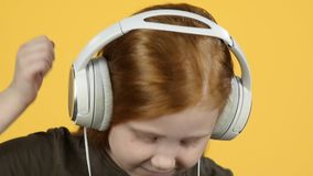 Close-up baby enjoying to music in big headphones and dancing , slow motion stock footage