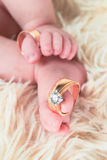 Close up of baby's feet with wedding rings. Newborn. Selective focus stock images