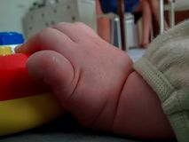 Close up of baby`s hand on play mat, holding colorful toy royalty free stock photo