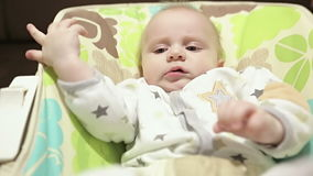 Close up baby shaking legs in the nursery rocking chair. stock footage