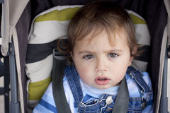 Toddler strapped up in stroller stock photo