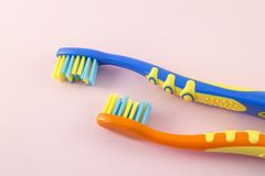 Close-up of baby toothbrushes on color background. Orange and blue baby toothbrushes on pink background. Closeup image Royalty Free Stock Photography