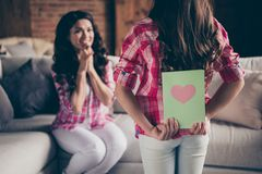 Close up back behind rear view photo two people mum little daughter giving postcard holiday morning sweet unexpected. Cute delighted wear pink plaid shirts flat royalty free stock image