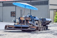Close up back of the blue machinery carry small stone with mixed with the asphalt For pouring on the floor to make a parking lot stock photo