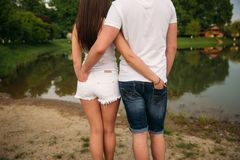 Close-up of back. Couple hold heir hands in back pockets royalty free stock photo