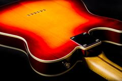 Close up of the back of an electric guitar. Close up of the back of a vintage electric guitar with a beautiful red to yellow sunburst paint job on Alder wood Royalty Free Stock Images