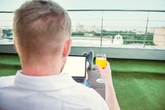 Close up back view businessman with drink comfortably working on laptop with white blank screen sitting on terrace with Urban Land Stock Photography