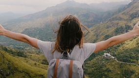 Close-up back view excited young tourist woman with backpack opening arms wide watching epic Sri Lanka mountains scenery. Happy amazed female traveler enjoying stock footage
