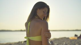 Close-up back view of happy Caucasian woman rubbing sunscreen in gorgeous tanned body in sunrays. Portrait of charming