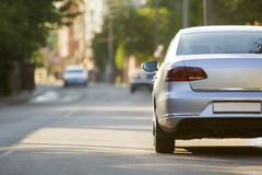 Close-up back view of new shiny expensive silver car moving along city street on blurred trees, cars and buildings background on s. Unny summer day. Comfortable stock image