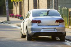 Close-up back view of new shiny expensive silver car moving along city street on blurred trees, cars and buildings background on. Sunny summer day. Comfortable royalty free stock images