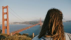 Close-up back view shot of young tourist woman with hair blowing in the wind enjoying epic sunset at Golden Gate Bridge. stock video footage