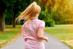 The back of a running woman in a park. Close up from the back of a young blonde woman running away from the camera on the road in a parkr Stock Image