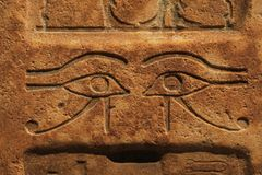 Stone wall with carved ancient Egyptian bas relief. Close up background of antique stone wall with carved ancient Egyptian bas relief of wadjet, Eye of Ra or stock images