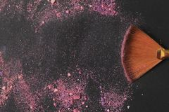 Close up. background image of a brush smears grains of powder on a black background royalty free stock images