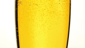 Close up pouring beer with bubbles in glass. Close up background of pouring beer, sparkling wine or champagne with bubbles in glass, low angle side view, slow stock video