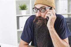 Close up of baffled man with long beard on the phone Stock Photo