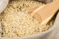Close up of bag burlap with brown rice and spoon Royalty Free Stock Images