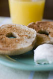 Close up of bagels on plate. Toasted bagels and cream cheese on plate with glass of juice Stock Photos