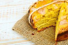 Close-up of baked pie with apples on sackcloth on a white wooden background. Rustic style. Fresh bakery. Close-up of baked pie with apples on sackcloth on a stock photos
