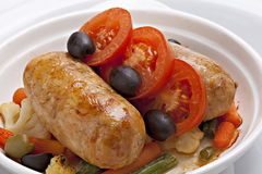 Close - up baked sausage with vegetables  in bowl Stock Images