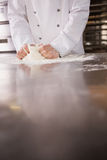 Close up of baker kneading dough on counter Royalty Free Stock Photo