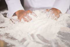 Close up of baker kneading dough on counter Royalty Free Stock Photography